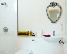 Pure white bathroom accented by brightly coloured towels, and a heart shaped, reclaimed silver mirror