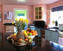 Kitchen restyle with bold colours: pastel pink walls, pastel blue cabinets, and a granite worktop offset by a fruit and flower display