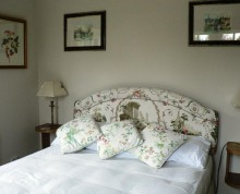Guest room showing dark-framed pictures, and white, patterned bedhead and cushions
